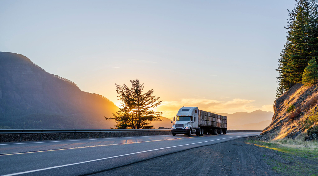 A truck drives away from the sunset in a setting with hills and trees.