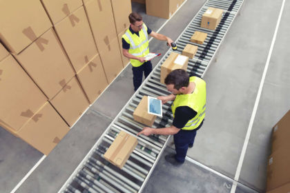 A team examines boxes on a conveyor belt