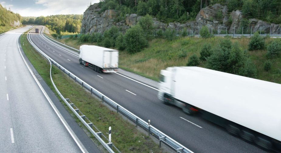 Two white trucks pass a rocky hill on a highway