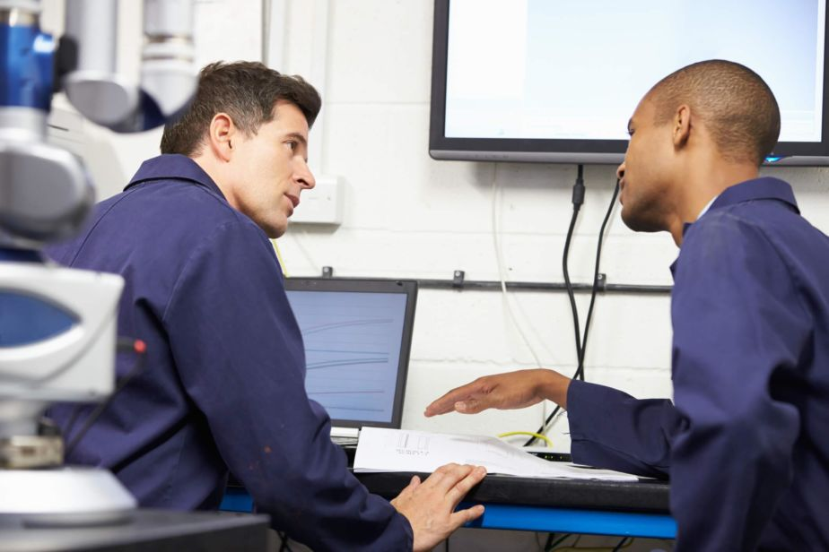 Two technicians discuss maintenance software in an office setting